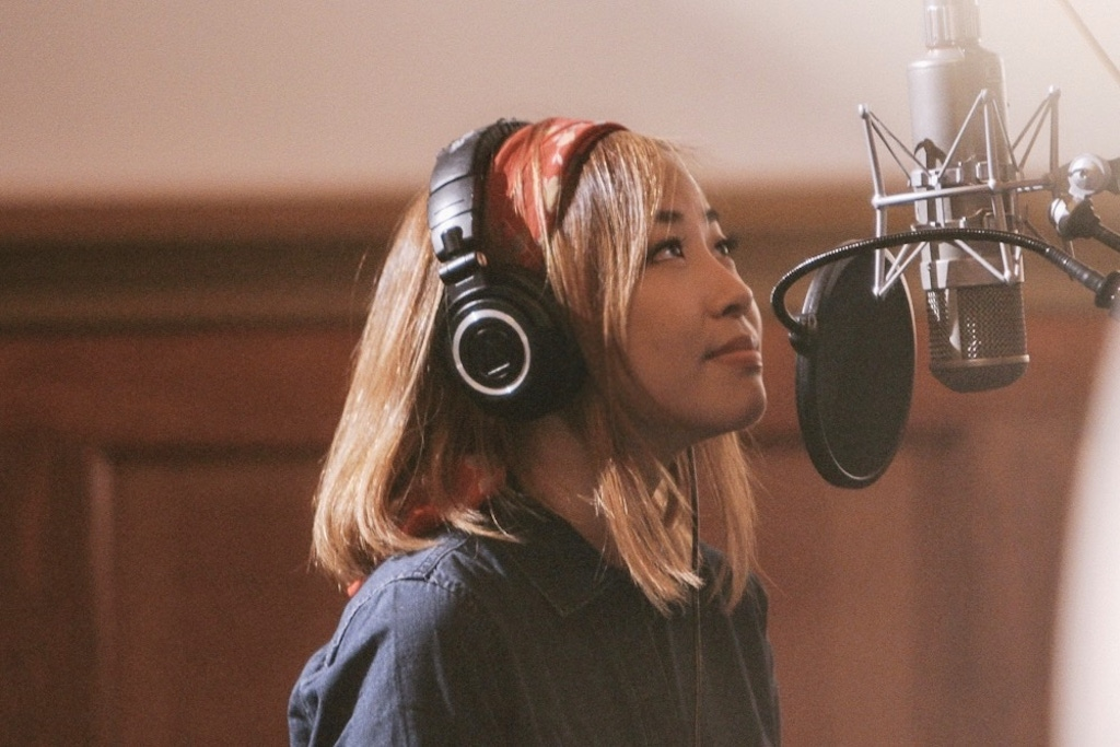 A Korean woman with blonde hair wearing a red bandana, headphones, and a dark denim shirt prepares to sing into a studio microphone.