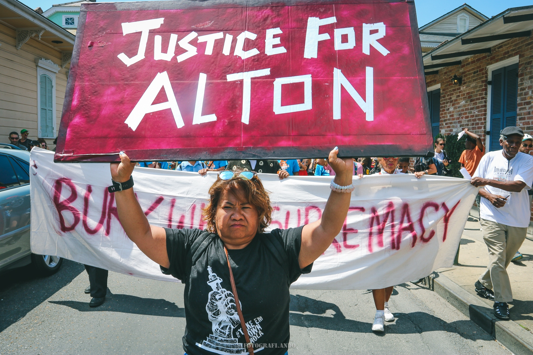 A woman of color holds up a large sign in cloudy red with the white-taped letters Justice For Alton. She stands in the street in front of marching protestors holding a white banner saying Bury White Supremacy.