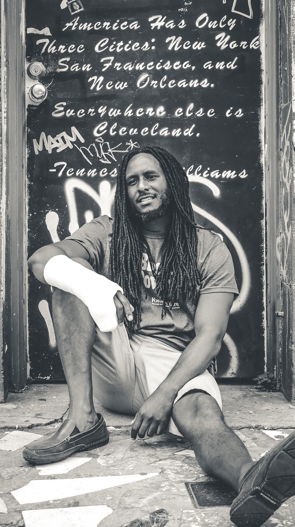 A black-and-white photo of a Black man with long dreadlocks sitting and leaning against a doorway painted with a Tennessee Williams quote in cursive. The man is wearing a T-shirt, light shorts, boat shoes, and has a cast on his right arm.
